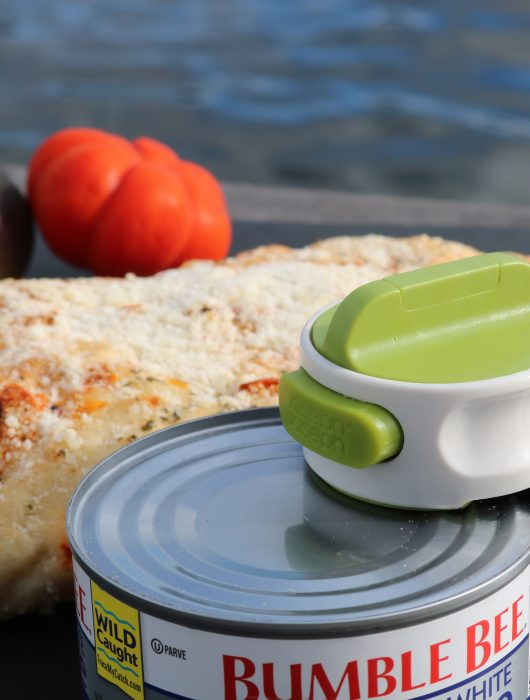 Mini can opener on a tuna fish can lid in front of a chunk of focaccia bread and and heir loom tomato.