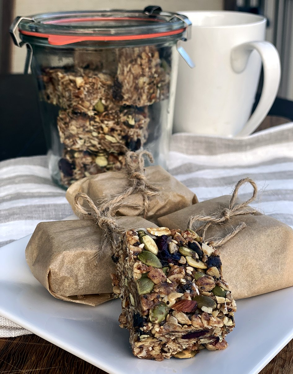 Crunchy seed and nut bars wrapped in parchment and tied with string on a striped towel. Stored in a air tight glass jar with mug behind.